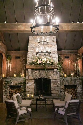 wedding-reception-lounge-wood-stacked-fireplace-mantle-with-pink-white-flowers-greenery-chandeliers