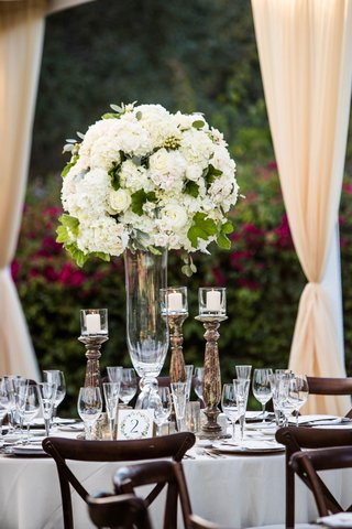 wedding-reception-tall-centerpiece-white-hydrangea-roses-greenery-wood-chairs-candles
