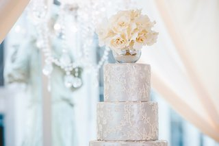 silver-wedding-cake-with-round-tiers-white-icing-and-mercury-glass-vase