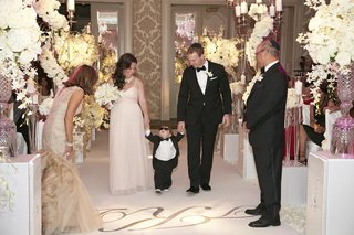 cute-little-boy-walking-down-aisle-between-couple