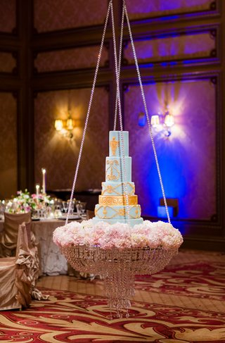 light-blue-and-gold-wedding-cake-on-top-of-chandelier-display-pink-peony-flowers-and-crystals