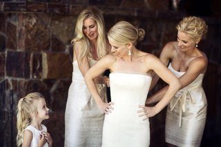 women-in-white-dresses-helping-bride-get-dressed