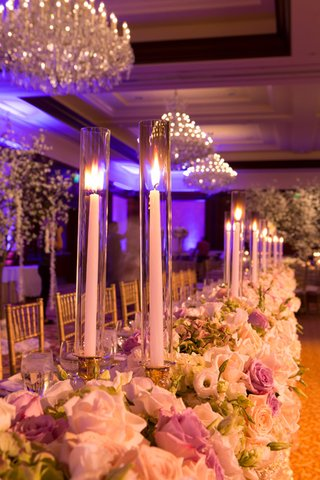 long-wedding-reception-head-table-with-white-purple-roses-mint-hydrangeas-taper-candles-on-gold