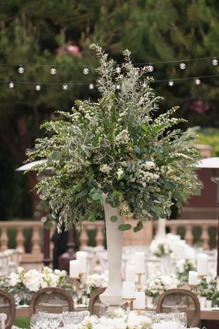 tall-greenery-wedding-centerpiece-white-flowers-and-green-leaves-white-vase-gold-candlestick