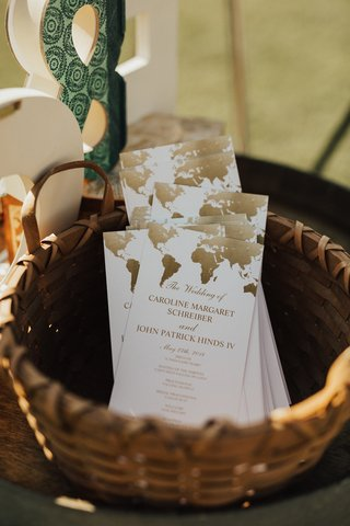 basket-of-wedding-ceremony-programs-with-world-map-in-gold-on-the-top