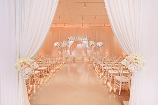 entrance-to-ceremony-with-white-curtains-held-back-by-blush-and-ivory-flower-arrangements