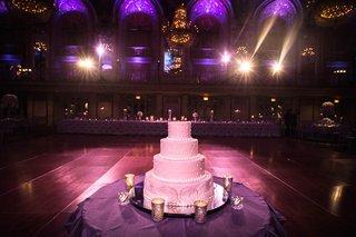 four-layer-wedding-cake-on-dance-floor-at-wedding-with-purple-lighting