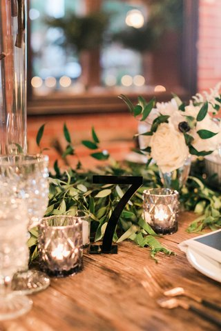 wood-wedding-reception-table-with-candle-votive-cut-crystal-glassware-black-table-number-cut-out