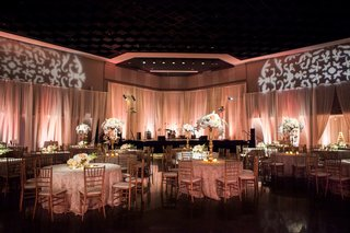 wedding-reception-with-peach-uplighting-white-centerpieces-round-tables-and-golden-chairs