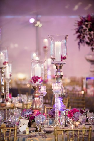 candlesticks-and-hurricanes-with-fuchsia-flowers-on-wedding-reception-table