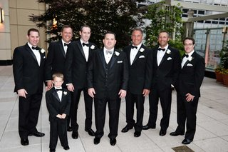 groom-and-ring-bearer-and-groomsmen-in-black-tuxedos-stand-in-chicago