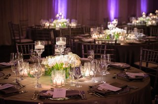 wedding-reception-round-table-white-flowers-tall-floating-candles-purple-lights-grey-linens