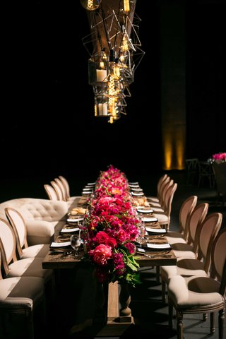 long-wooden-head-table-bright-pink-floral-runner-geometric-lighting-concept-dark-reception-space