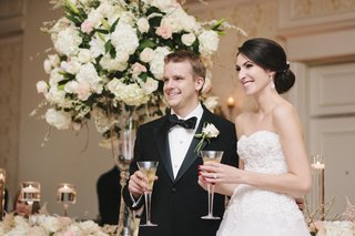 bride-and-groom-in-formal-attire-smile-with-champagne-at-reception