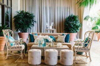 ocean-inspired-wedding-wicker-armchair-white-pouf-blue-tan-pillows-orchid-decorations-on-table