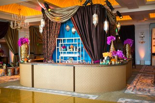 moroccan-style-engagement-party-with-brown-patterned-gold-draping-behind-bar-with-diamond-design