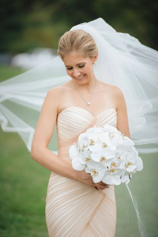 bride-in-strapless-mark-zunino-blush-mermaid-gown-holding-bouquet-white-orchids-veil-blowing-in-wind