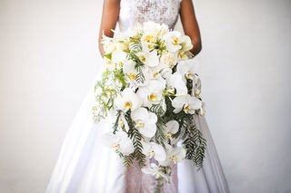 bride-in-wedding-dress-a-line-holding-large-cascade-bouquet-with-orchid-flowers-fresh-greenery