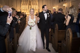 bride-and-groom-smiling-at-wedding-guests-in-pews-at-catholic-church-ceremony-overskirt-wedding-gown