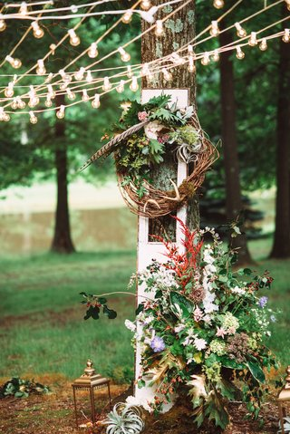outdoor-wedding-reception-with-a-branch-wreath-with-leaves-feathers-and-flowers-against-a-tree