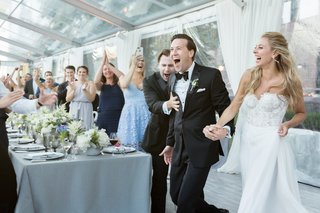 guests-cheer-as-bride-and-groom-enter-tented-wedding-reception
