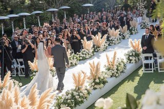 outdoor-wedding-ceremony-white-aisle-runner-pampas-grass-white-flowers-bride-processional-father