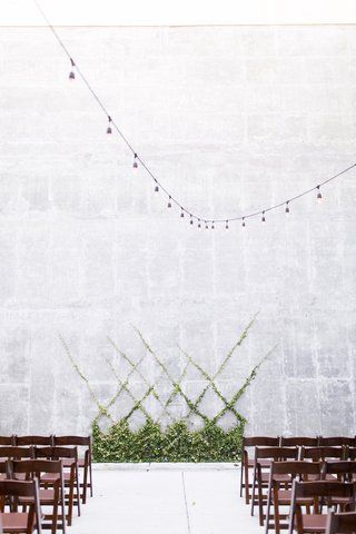 brown-wooden-chairs-facing-concrete-wall-string-lights-overhead-greenery-cross-hatch-pattern-at-alta