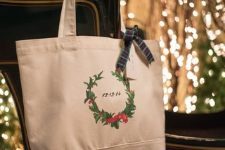 white-tote-bag-with-wedding-date-and-holly-wreath-decoration-tied-with-plaid-ribbon
