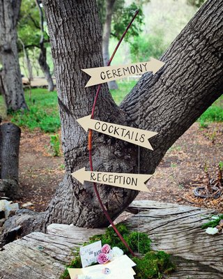 outdoor-wedding-with-direction-signs-made-of-arrow-cutouts-placed-on-a-bow