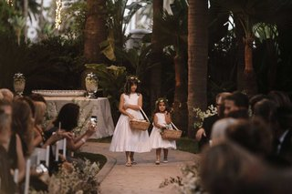 flower-girls-in-white-dresses-wicker-baskets-with-ribbon-handles-flower-crowns-stone-aisle-ceremony