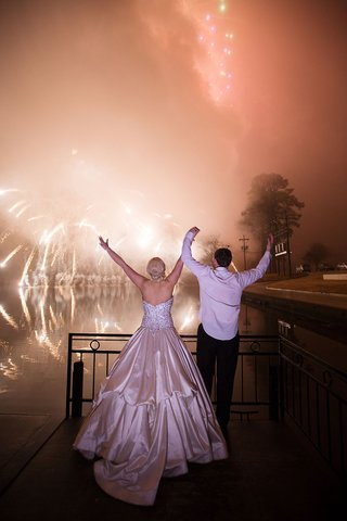 bride-and-groom-holding-hands-with-ball-gown-firework-show-over-water-in-distance-over-bayou