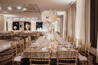 gold-chairs-and-gold-metallic-overlay-on-navy-blue-linen-tall-centerpiece-white-flowers-candles-low