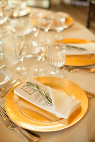 gold-plates-for-wedding-menu-with-sprig-of-greenery