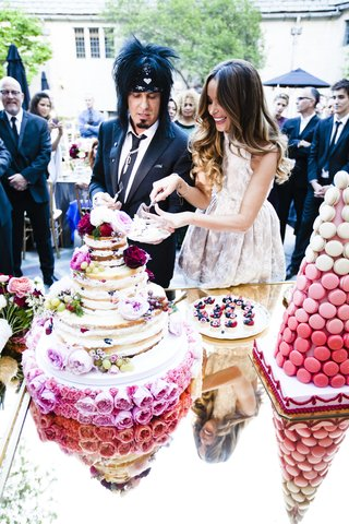 bride-and-groom-cut-naked-cake-at-outdoor-reception