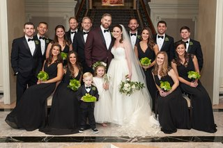groom-in-maroon-tuxedo-with-bride-in-a-line-gown-and-groomsmen-in-tuxedos-bridesmaids-in-black-dress