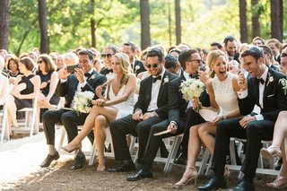 bridesmaids-and-groomsmen-sitting-in-front-row-white-dresses-outdoor-wedding-laughing-guests-smiling