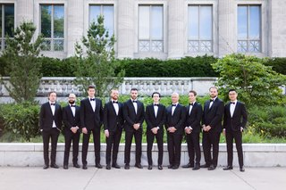 groom-and-groomsmen-in-front-of-chicago-wedding-venue-classic-tuxedo-attire