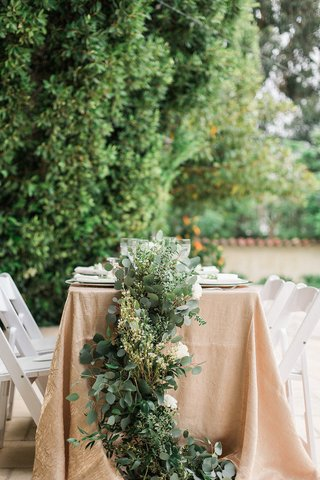 wedding-reception-at-eden-gardens-ca-with-foliage-runner-on-table-with-golden-taffeta-tablecloth