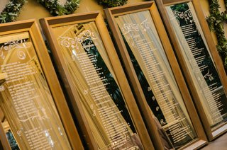 white-seating-chart-lettering-on-large-rectangular-mirrors-in-gold-frames
