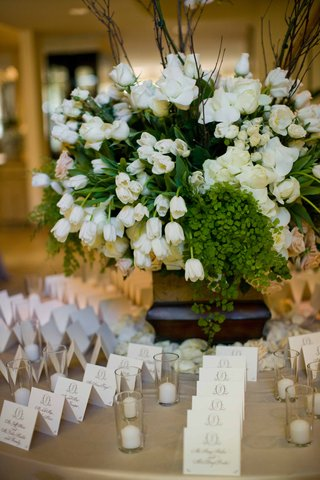 table-with-escort-cards-and-tulip-and-rose-arrangement