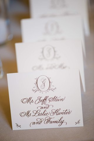 white-escort-card-with-brown-handwritten-calligraphy