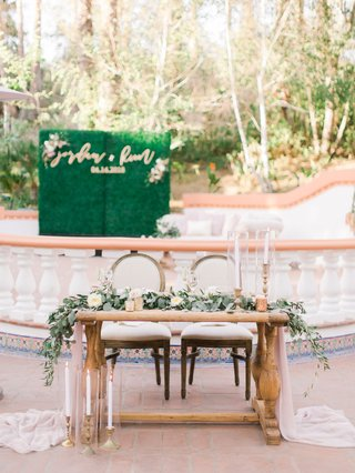 wedding-reception-outdoor-courtyard-wood-sweetheart-table-greenery-gold-candlesticks-spanish-tile