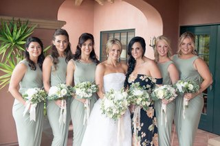 bride-in-strapless-wedding-dress-with-maid-of-honor-in-pattern-flower-dress-and-bridesmaids-in-green