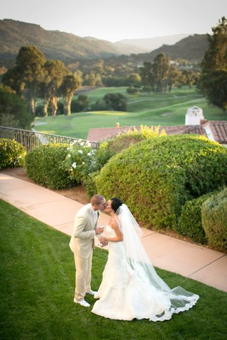 bride-and-groom-kiss-on-lawn-with-golf-course-view