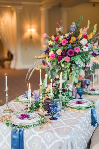 large-centerpieces-with-a-rainbow-of-flowers-mixed-metal-candlesticks-colorful-glassware