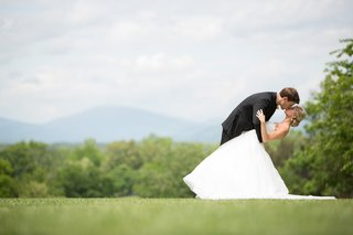 groom-dips-bride-in-ball-gown-in-grass-meadow