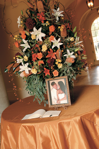 guest-book-photo-and-flowers-placed-on-orange-table