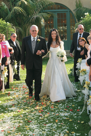 bride-and-dad-walk-down-aisle-covered-with-flower-petals