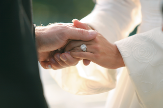 bride-wears-engagement-ring-and-holds-hands-with-groom