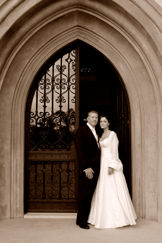 couple-stands-in-front-of-dramatic-arched-doorway
